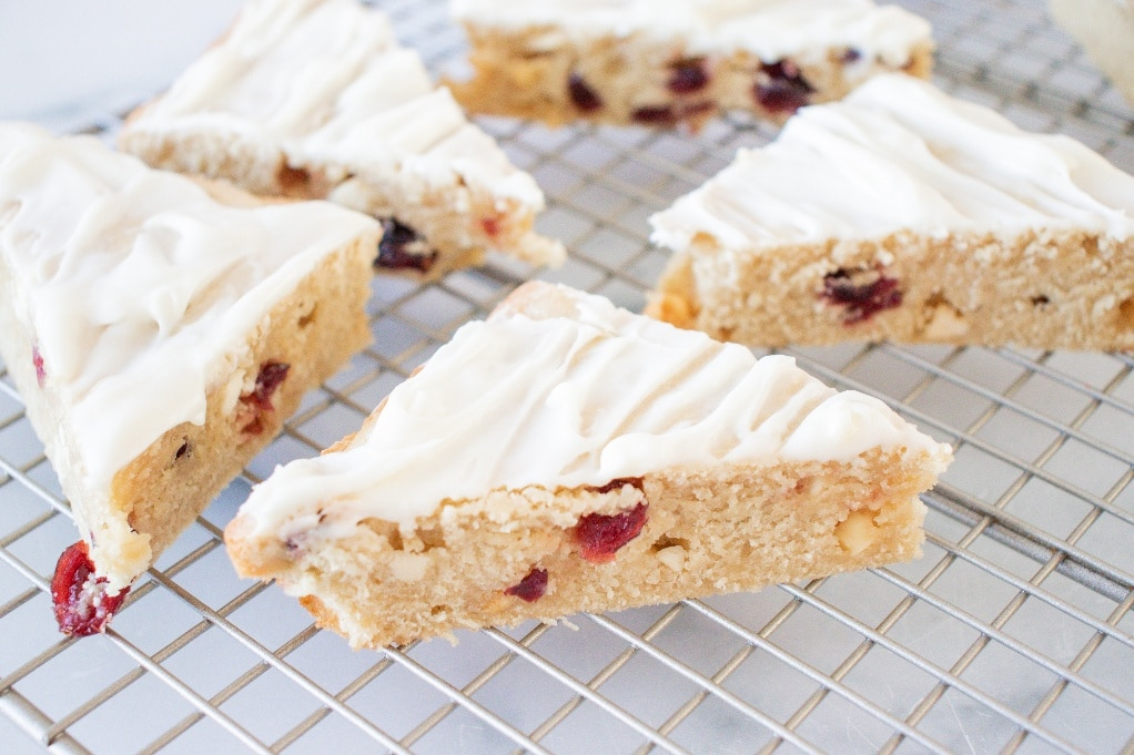 Sliced cranberry bliss bars frosted with sweet cream cheese on a cooling rack.