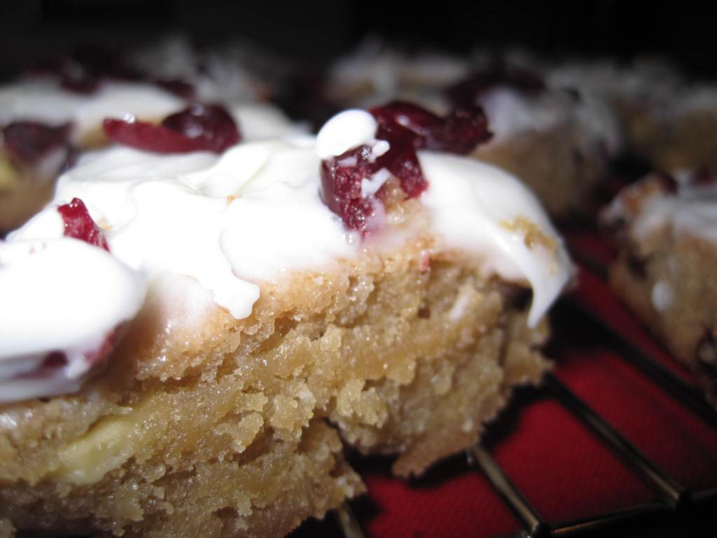 Copycat Starbucks Bliss Bars are triangular pieces of cookie with cake crust are topped with a decadent cream cheese frosting mixed with white chocolate and dried cranberries.