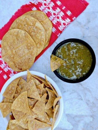 Homemade tomatillo salsa verde with baked tortilla chips