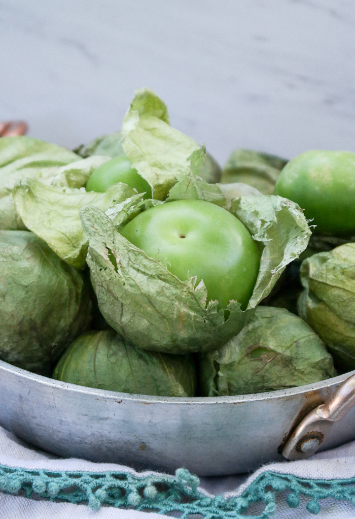 Fresh tomatillos in a stainless steel bowl.