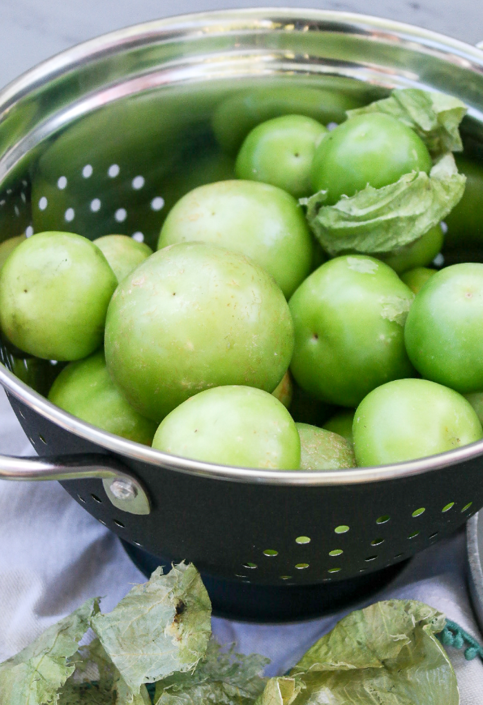 Fresh tomatillos in a colander to be washed.