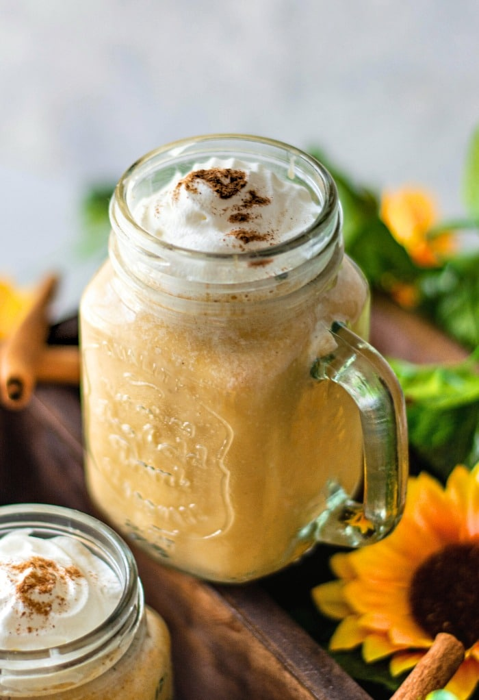 Pumpkin smoothie in a mason jar topped with whipped cream.