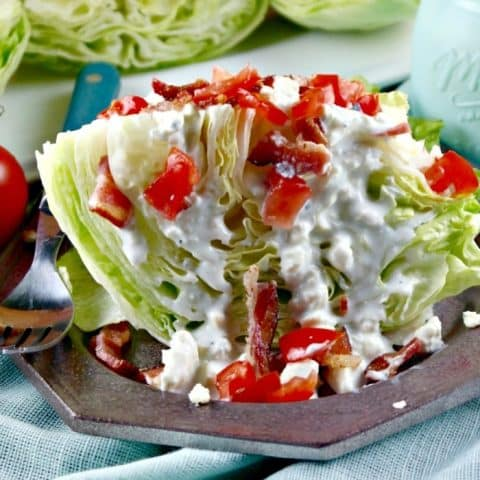 Wedge salad topped with blue cheese dressing and tomatoes