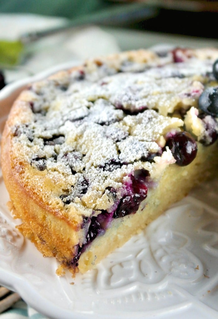 Blueberry coffee cake without streusel topping on a white cake plate