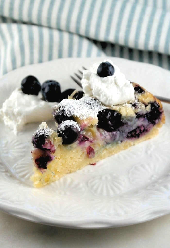 Slice of homemade blueberry coffee cake with whipped cream