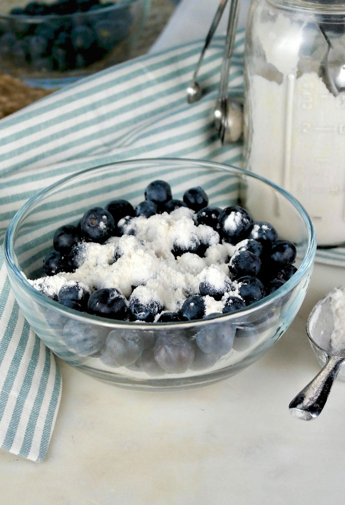 Flour added to blueberries for baking in a cake