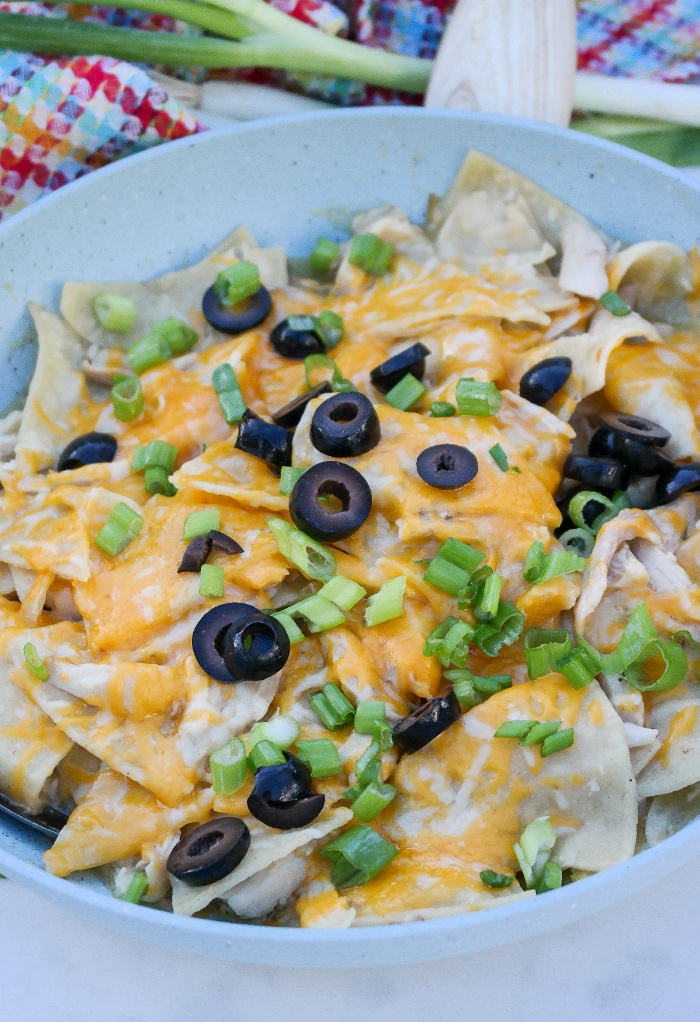 A light blue skillet with enchiladas topped with olives.