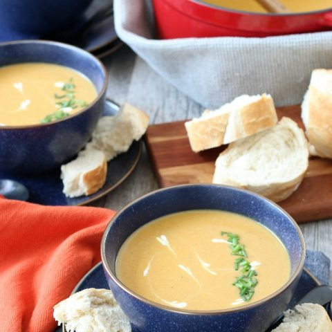 Finished sweet potato soup with coconut milk in a bowl with some bread on the side.