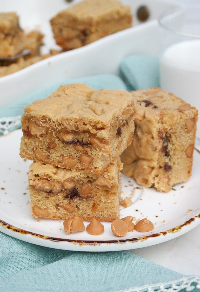Sliced cookie bars on a plate with milk on the side.