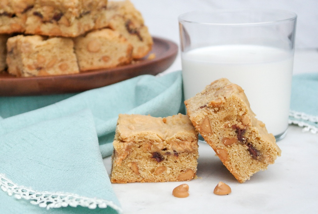 Peanut butter cookie bars with a clear glass of milk.