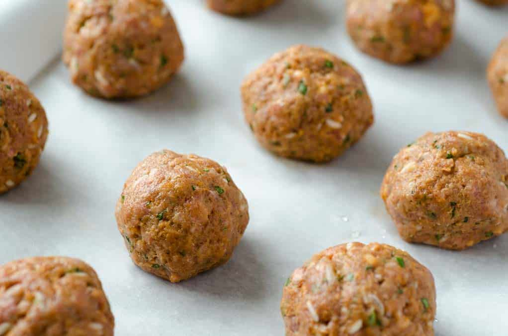 round uncooked meatballs on a baking sheet for albondigas soup