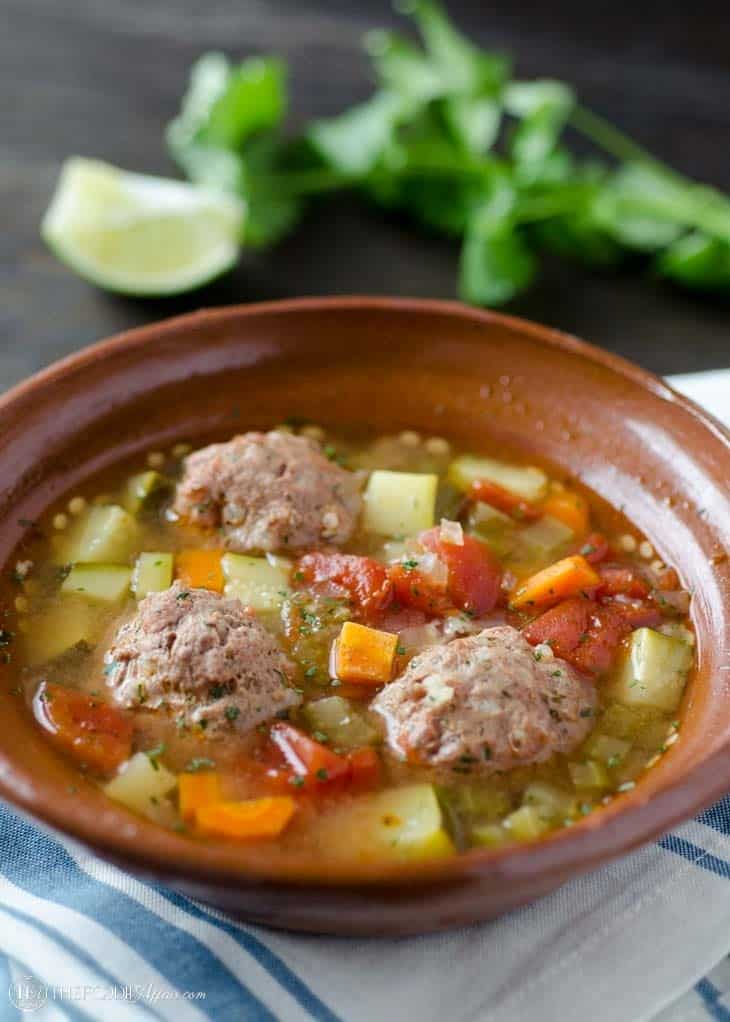 Albondigas soup in a brown bowl with line and cilantro on the side of the dish