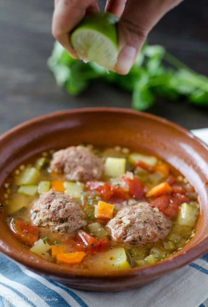 Albondigas soup in a brown bowl with fresh lime juice squeezed over the food