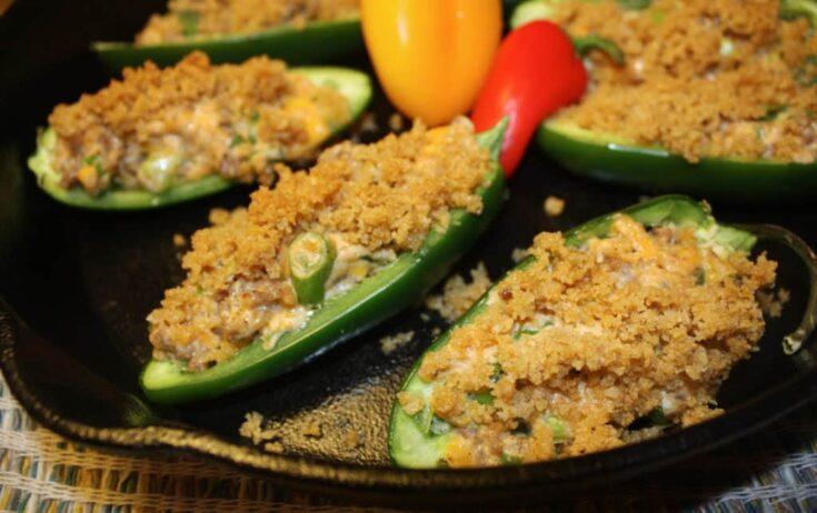 sausage stuffed jalapeños in a cast iron pan