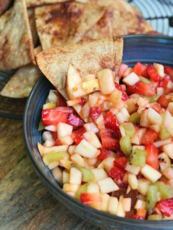 A cinnamon tortilla chip dipped in a fruit salsa bowl.