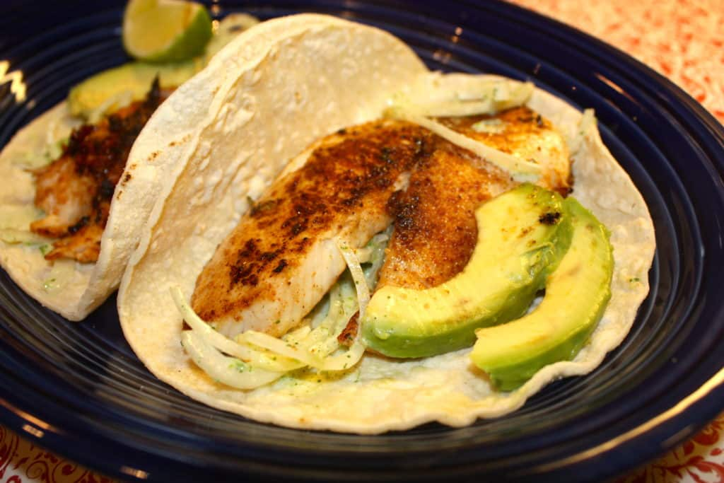Tilapia Fish Tacos with blackened seasoning and onion-jalapeno topping