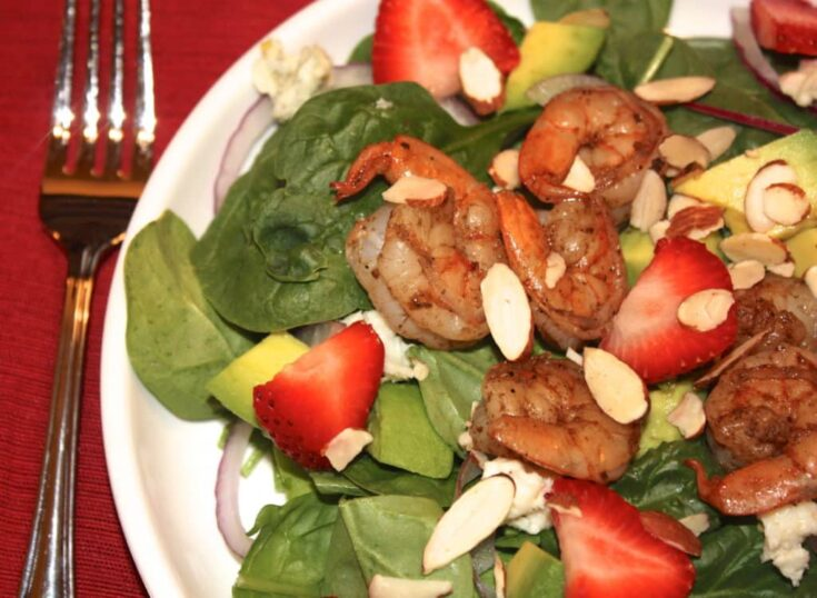 Easy spinach strawberry salad on a white plate