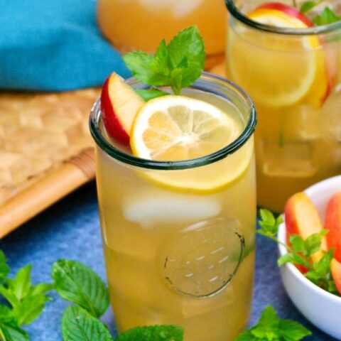 Peach lemonade in clear glasses with lemon slice