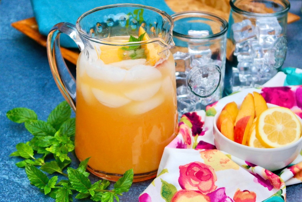 Clear pitcher of lemonade made with fresh peaches