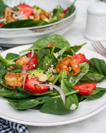 Spinach Strawberry salad on a white plate ready to eat.