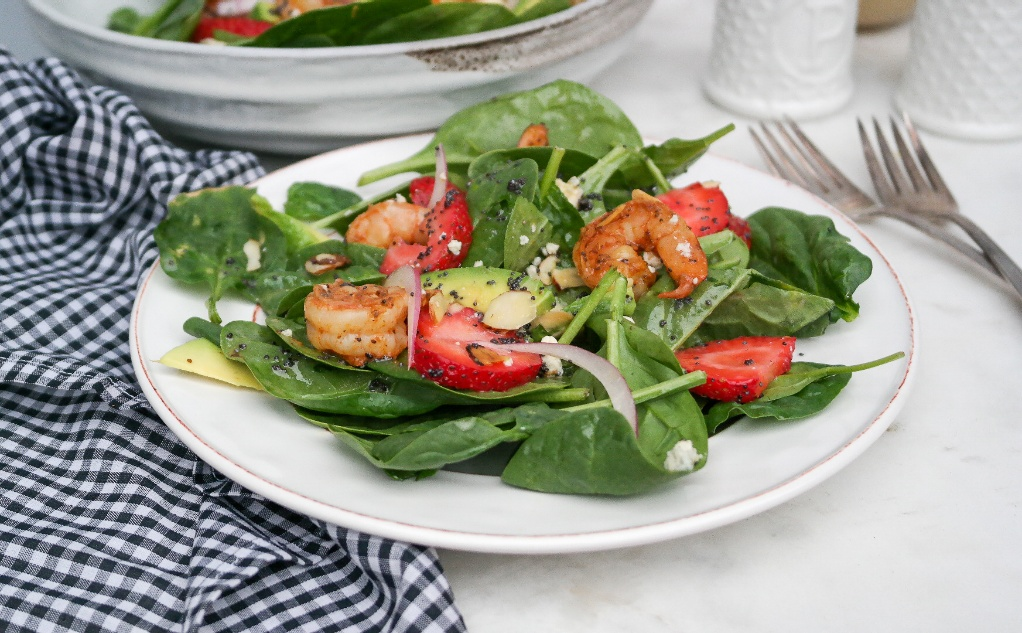 Spinach avocado salad with shrimp on a white salad dish.