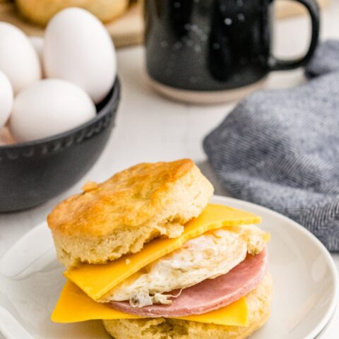 Biscuit sandwich on a white plate filled with egg, ham and cheese.