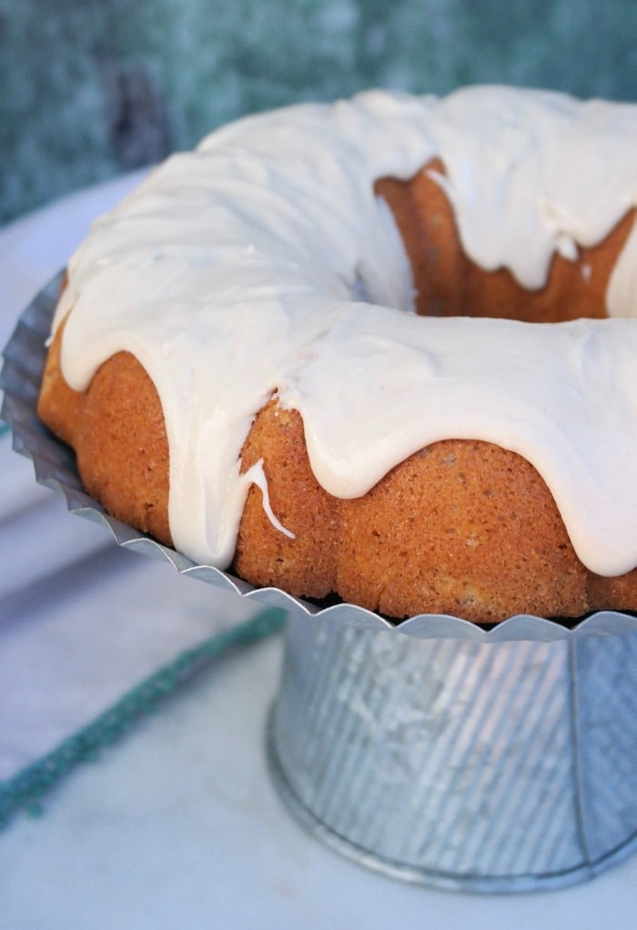 Spice bundt cake topped with icing on an aluminum cake plate.