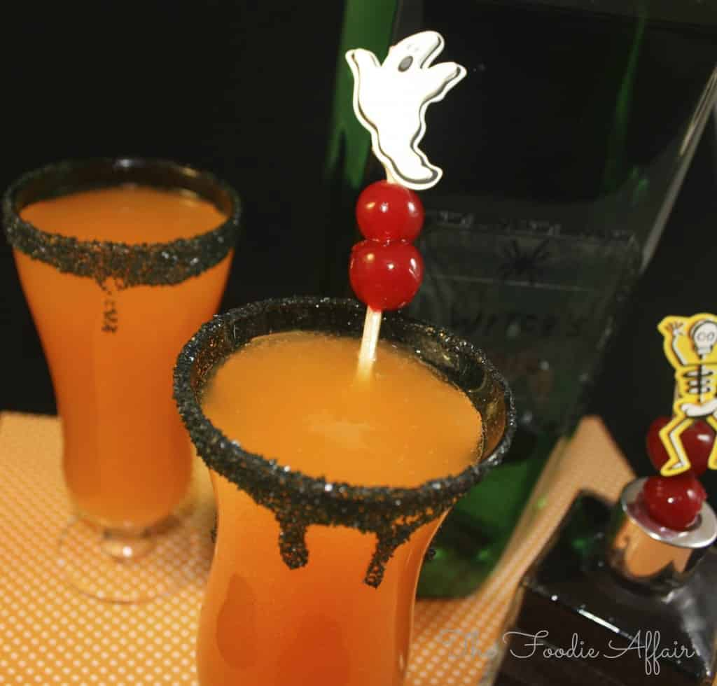 Halloween Cocktail in a clear glass with black rimmed sugar