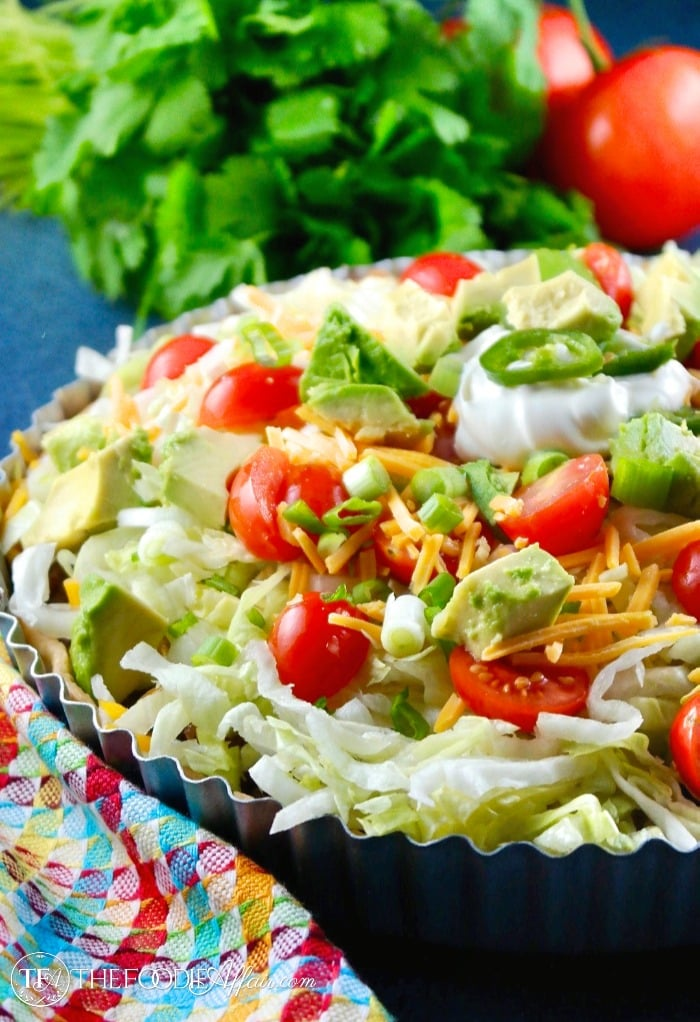 taco pie topped with lettuce and tomatoes