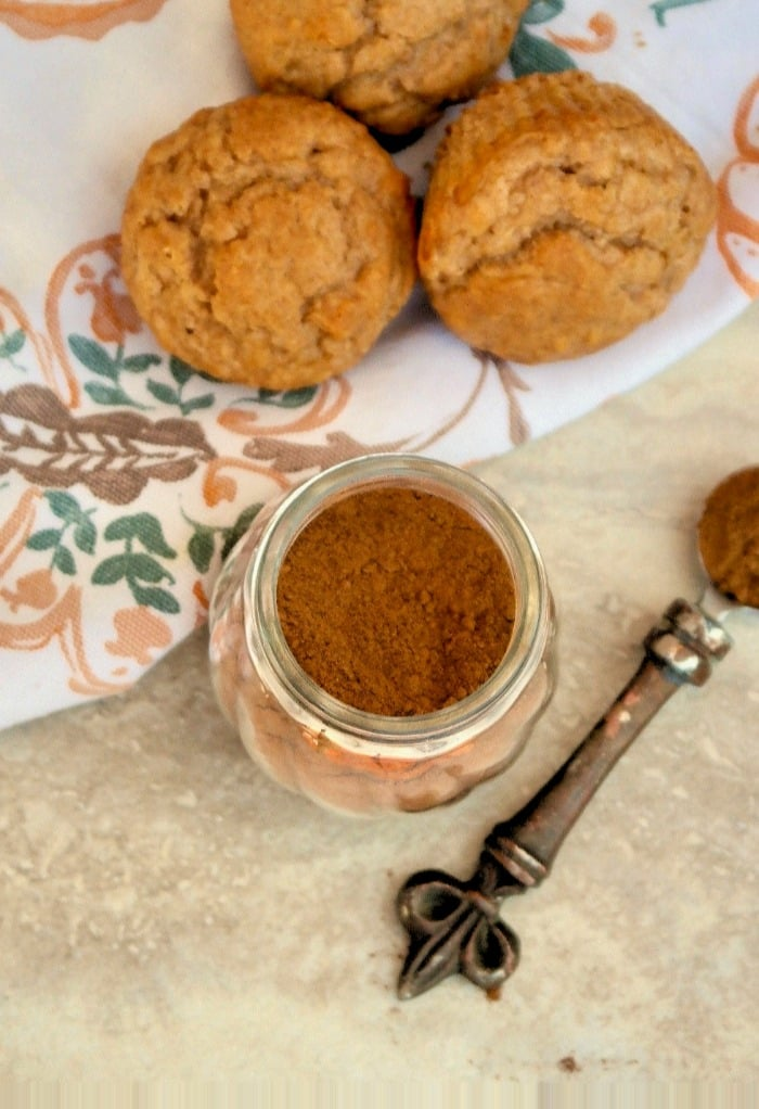 clear jar of pumpkin pie spice with muffins on the side