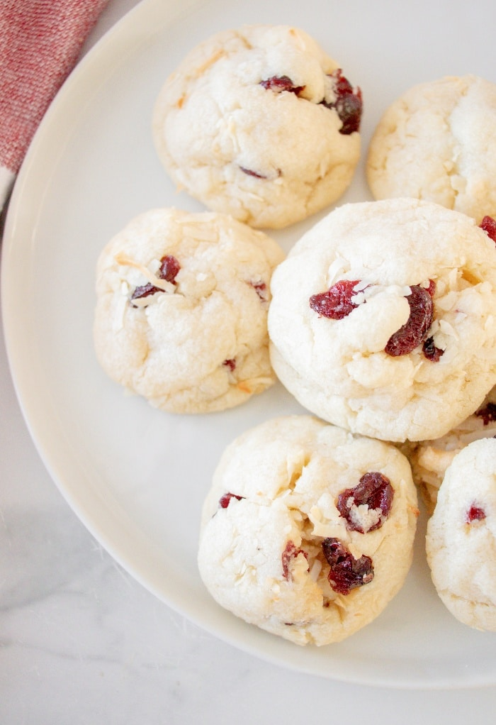 A top view of cranberry cookies on a white plate ready to eat.