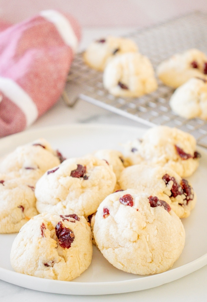 A white plate full of cranberry coconut cookies with cookies cooling on a backing rack in the background.