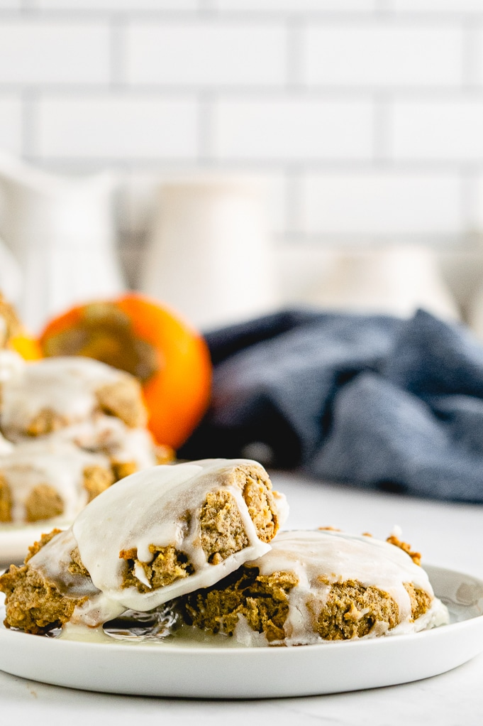 A white serving plate with persimmon cookies with a fresh persimmon in the background.