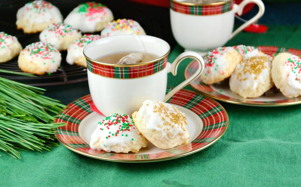 Holiday cookies on a plate with a cup of tea on the side