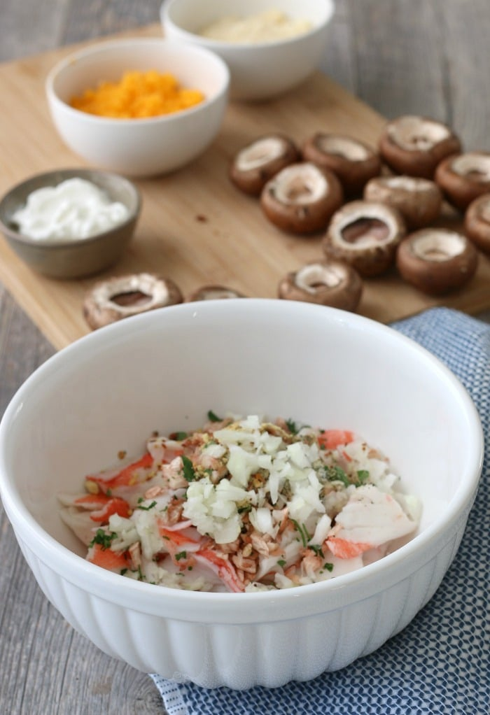 This image shows the stuffed mushroom with crab mixture being combined and ready to be stuffed into mushroom caps.