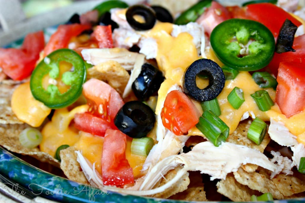 platter of nacho cheese sauce on tortilla chips with tomatoes, jalapeños and olives
