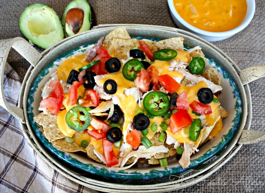 Nacho cheese sauce platter with jalapeños, olives, tomatoes and shredded chicken