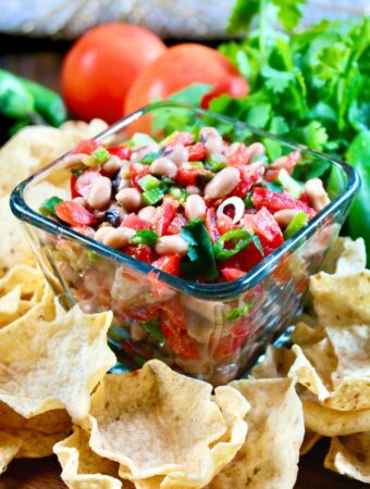 Texas caviar dip in a clear bowl with scoop chips around the bowl on a wood platter.