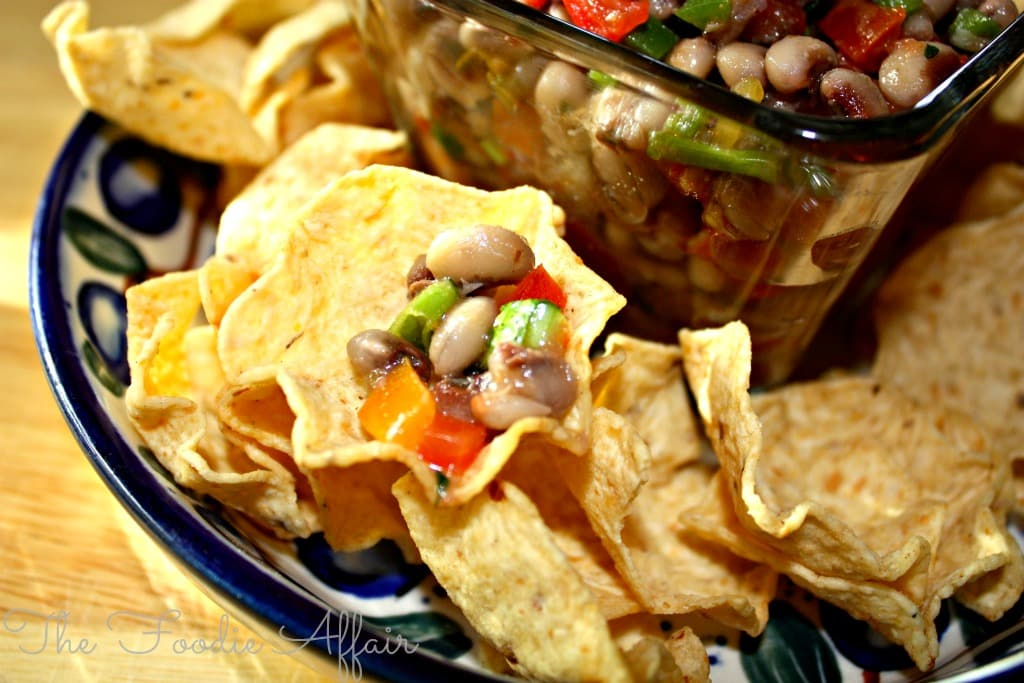 Texas caviar dip on a plate with scoop tortilla chips