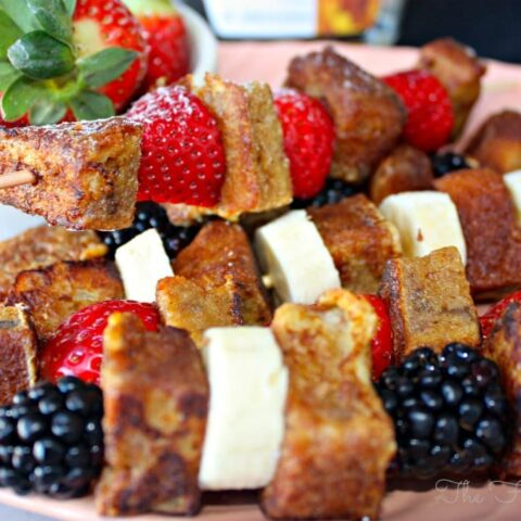 French Toast Kabobs with fruit on a pink platter