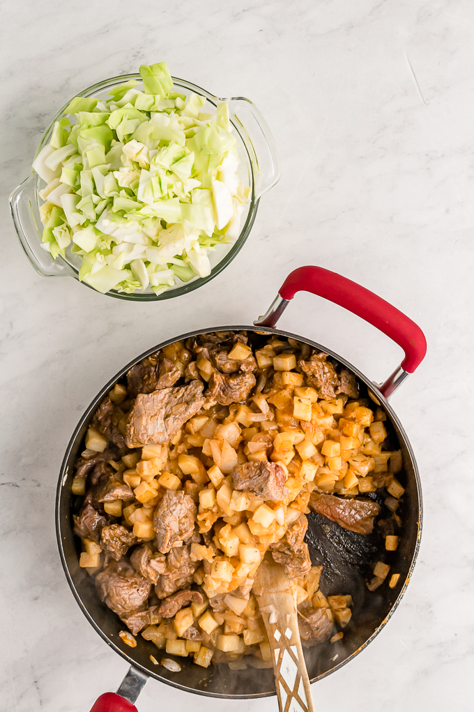 Meat and potato filling for hand pies in a skillet.