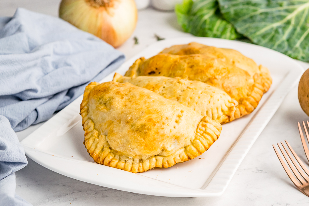 Cooked meat pies on a white serving dish.