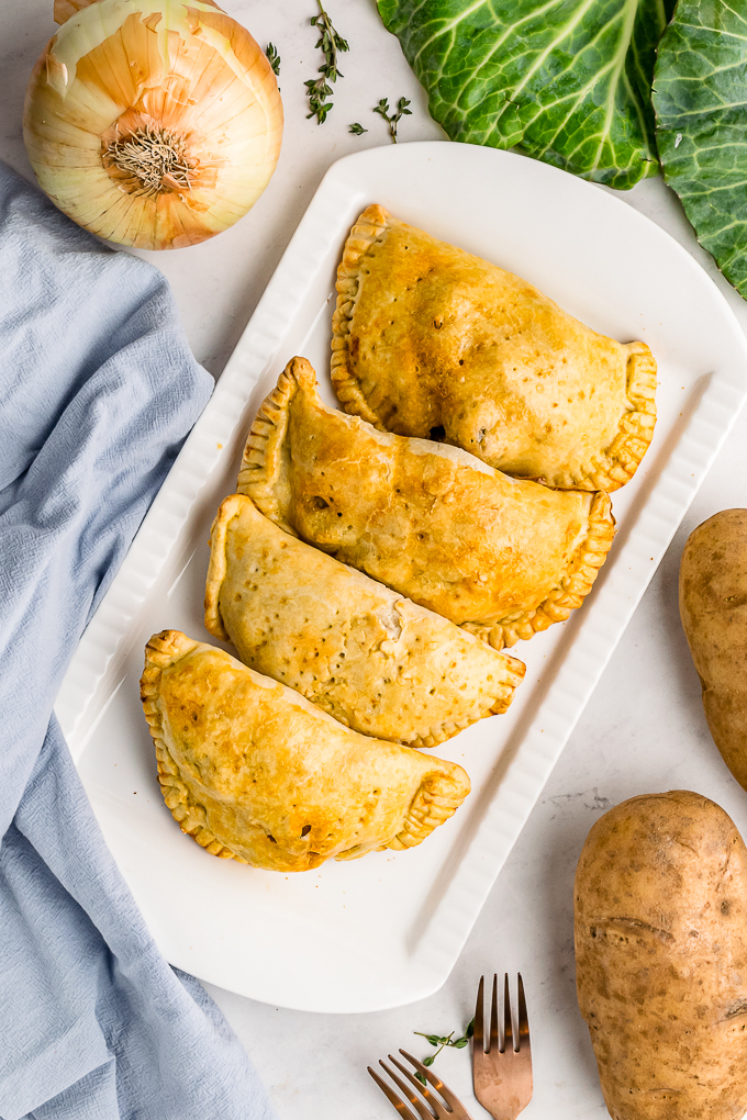 Baked meat pies on a white serving platter.