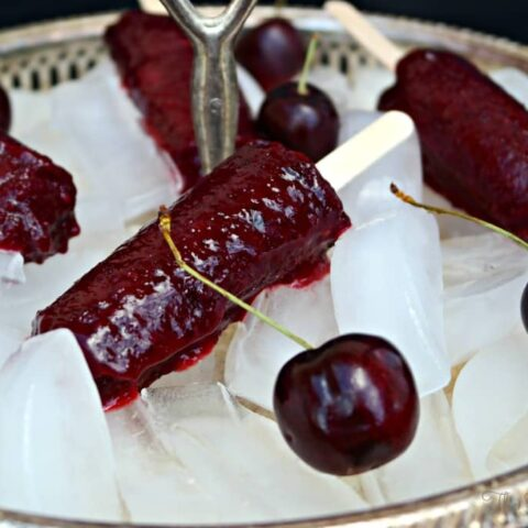Cherry Limeade Popsicles on a tray filled with ice