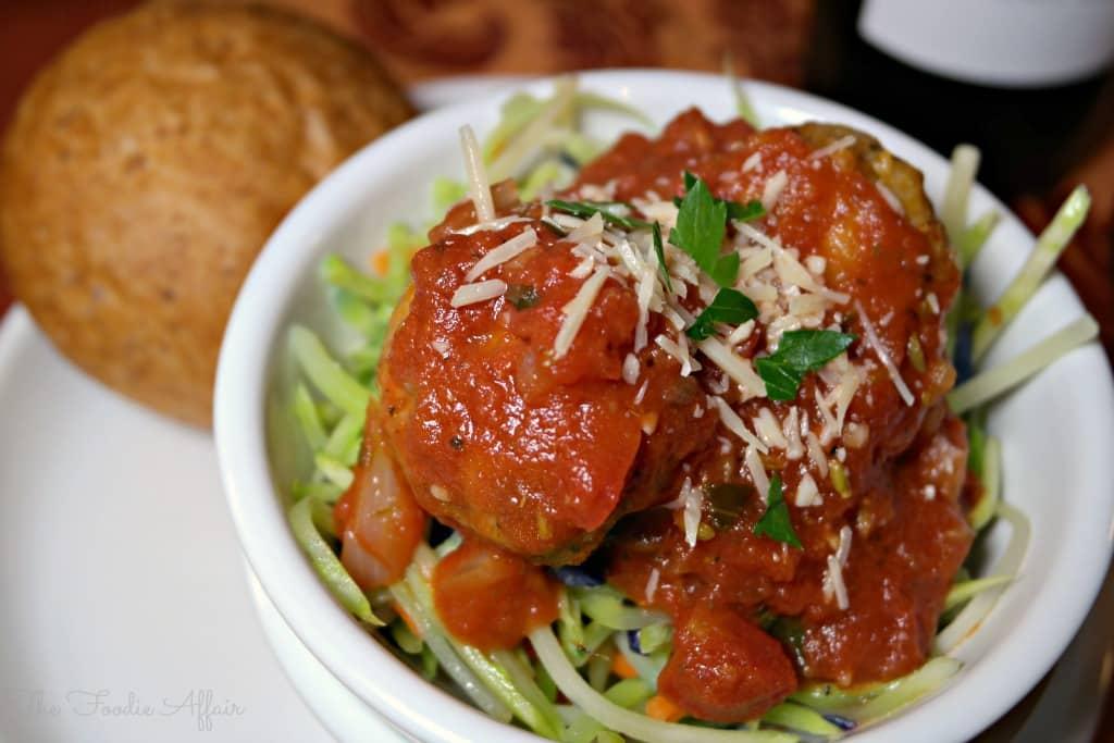 Turkey meatballs over broccoli slaw in a white bowl
