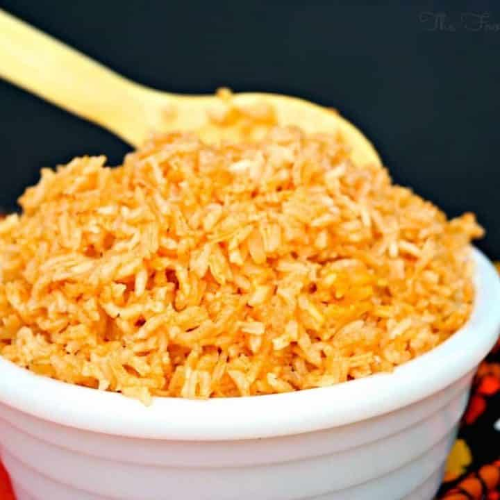 Spanish rice in a white serving bowl with a wooden spoon
