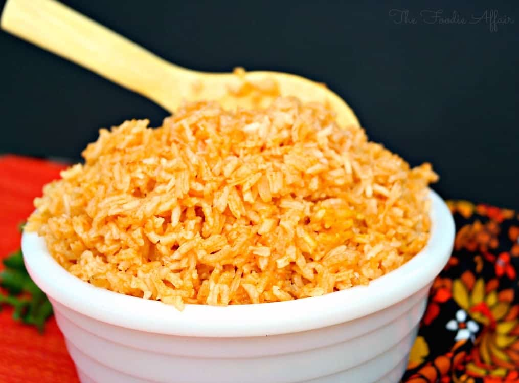 Spanish rice in a white bowl with wooden spoon