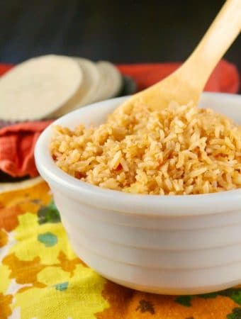 Mexican rice in a white bowl with wooden spoon