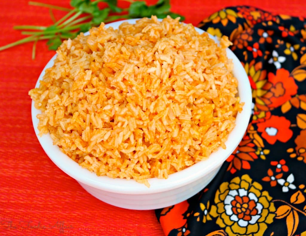 Spanish rice in a white bowl with orange napkin