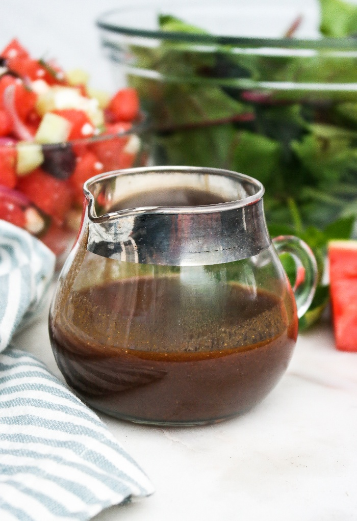 Dijon balsamic salad dressing in a small clear pitcher with a silver rim.